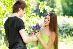 Man presenting blue flowers to a woman Royalty Free Stock Image