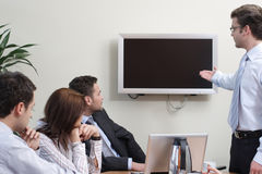 Man presenting data on screen to group