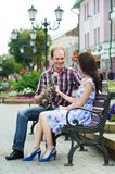 Man presenting flower to woman on a date Royalty Free Stock Photos