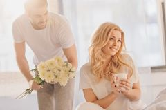 Man presenting flowers for beautiful girlfriend. While she drinking coffee at morning royalty free stock image