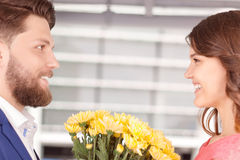 Man presenting flowers to his girlfriend. Soft glance. Young smiling men giving some beautiful flowers to his lovely girlfriend Stock Images