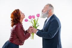 Man presenting flowers to woman Stock Images