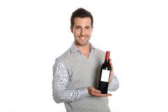 Man presenting a good wine bottle. Happy winegrower showing wine bottle to camera stock photos