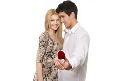 Man presenting jewelry in red case to girl Stock Image