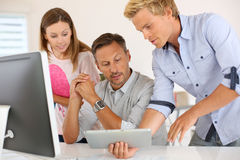 Man presenting results at colleagues on tablet Stock Image