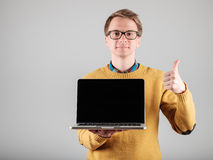 Man presenting something on blank laptop screen. Young hipster presenting your product on a laptop screen  on gray background Royalty Free Stock Image