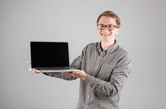 Man presenting something on blank laptop screen. Young hipster presenting your product on a laptop screen  on gray background Stock Image