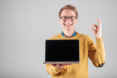 Man presenting something on blank laptop screen. Young hipster presenting your product on a laptop screen isolated on gray background Stock Photography