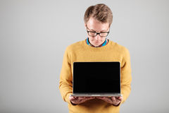 Man presenting something on blank laptop screen. Young hipster presenting your product on a laptop screen isolated on gray background Royalty Free Stock Photo