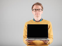 Man presenting something on blank laptop screen. Young hipster presenting your product on a laptop screen isolated on gray background Royalty Free Stock Photography