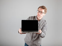 Man presenting something on blank laptop screen. Young hipster presenting your product on a laptop screen isolated on gray background Stock Images