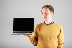 Man presenting something on blank laptop screen. Young hipster presenting your product on a laptop screen isolated on gray background Stock Photo
