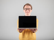 Man presenting something on blank laptop screen. Young hipster presenting your product on a laptop screen isolated on gray background Royalty Free Stock Images