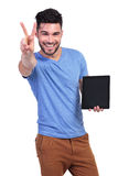 Man presenting a tablet pad and making the victory sign Stock Images