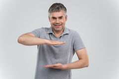 Man presenting your product isolated over white background. Royalty Free Stock Image
