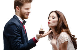 Man presents birthday sponge cake to his girlfriend Stock Image