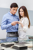 Man presents engagement ring to his woman. Man presents engagement ring to his women at jeweler's shop. Concept of wealth and luxurious life royalty free stock images
