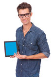 Man presents tablet. Portrait of a casual young man presenting his tablet and smiling to the camera. on white background Royalty Free Stock Images