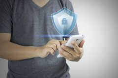 Man press on smart phone with protection of virus and hacking and cracking concept stock image