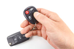 Man presses button on the garage door remote control on a white background Stock Photo