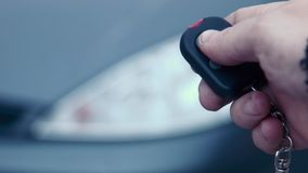 The man presses the button of the security alarm system in the car. The man switch on and switch off the autoalarm system stock footage