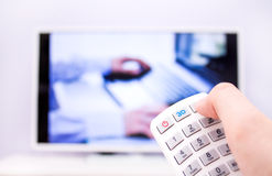 Man presses the 3D button on the remote control. Stock Image