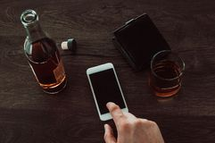 A man presses a finger on a mobile phone. Next on the table is a glass of whiskey, a bottle of whiskey and a purse stock images
