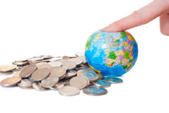 Man presses his finger on the globe. The man pressed his finger on a globe on the background of the money Royalty Free Stock Images