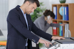 Man pressing amount paper to be copied Stock Photography
