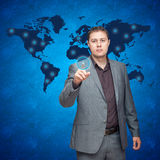 Man pressing buttons. Business man pressing buttons with the world map in the background Royalty Free Stock Images