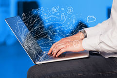 Man pressing notebook laptop computer with doodle icon cloud sym. Man pressing notebook laptop computer with doodle icon media cloud symbols Royalty Free Stock Photo