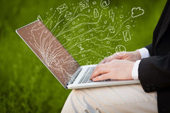 Man pressing notebook laptop computer with doodle icon cloud sym. Man pressing notebook laptop computer with doodle icon media cloud symbols Royalty Free Stock Photography