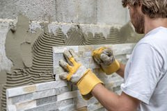 Man pressing an ornamental tile into a glue on a wall Royalty Free Stock Photography