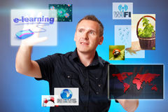 Man pressing screen. With e learning, other displays with miscellaneous subjects flying around Royalty Free Stock Images