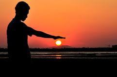 Man pressing the sun using his hand stock photos