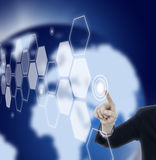 Man pressing touchscreen button in space. Hand pressing hexagon touch screen in space with blue world background Stock Photos