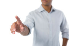 Man pretending to touch an invisible screen against white background Royalty Free Stock Images