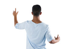 Man pretending to touch an invisible screen against white background Stock Photos
