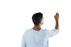 Man pretending to touch an invisible screen against white background Stock Images