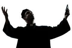 Man priest praying silhouette Stock Photos