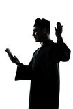 Man priest silhouette reading bible Stock Photo