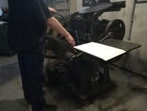 Antique printing machine. Man prints newspapers royalty free stock image