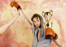 Man with prize on colorful background. Boxer with serious face. Man with messy hair on colorful background. Boxer with serious face holds golden prize and puts royalty free stock photos