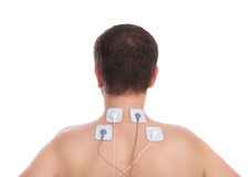 Man with problems in the neck and in the  massage makes electrostimulator. Royalty Free Stock Photo