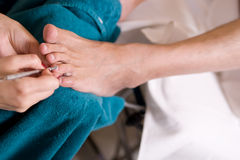 Man and  the procedure of pedicure Royalty Free Stock Photos