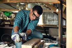 Man in the process of wood processing manual planing machine in the home workshop, manual labor, home craftsman royalty free stock images