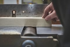 The man processes bar from a light tree on the jointer plane. Joiner Stock Image
