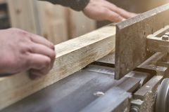 The man processes bar from a light tree on the jointer plane. Joiner furniture production Stock Images