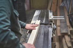 The man processes bar from a light tree on the jointer plane. Men hands of a Board in the background Royalty Free Stock Image