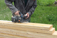 The man  processes a board a electric planer outdoors Stock Images